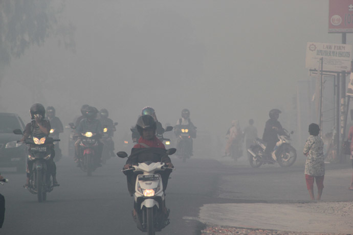 Indonesian motorists travel under a blanket of haze in Pekanbaru city, capital of Riau province on Sumatra island on June 20, 2013. (AFP Photo)