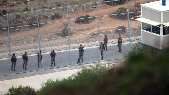 Spanish troops patrol the fenced perimeter of the Spanish enclave of Ceuta (AFP Photo)