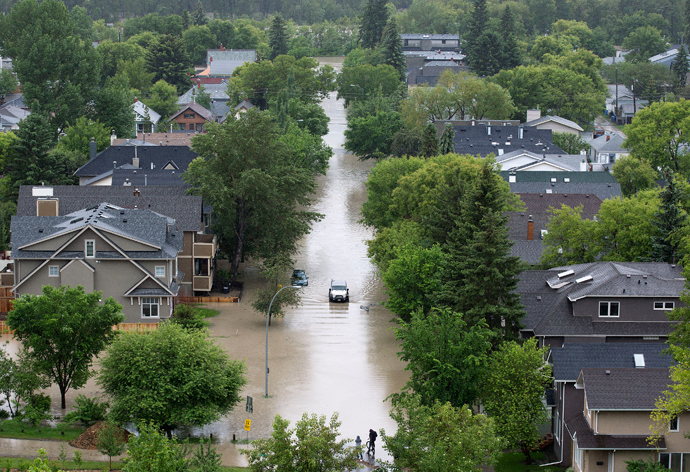 A vehicle drives down a flooded street in the neighbourhood of Sunnyside in Calgary, Alberta June 21, 2013 (Reuters / Todd Korol)