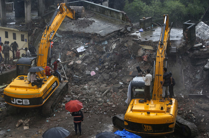Rescue workers use excavators to scour the debris for survivors at the site of a collapsed residential building in Mumbra, in Thane district, on the outskirts Mumbai June 21, 2013. (Reuters/Vivek Prakash)