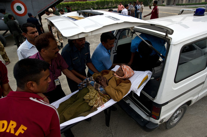 Indian disaster relief personnel assist an elderly woman into an ambulance after being evacuated from flood-hit areas at the Jolly Grant Airport in Dehradun, state capital of Uttarakhand on June 21, 2013. (AFP Photo)