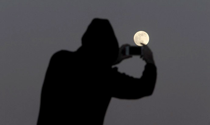 A man takes pictures of the full moon on the Spanish Canary island of Tenerife on June 22, 2013. (AFP Photo / Desiree Martin)