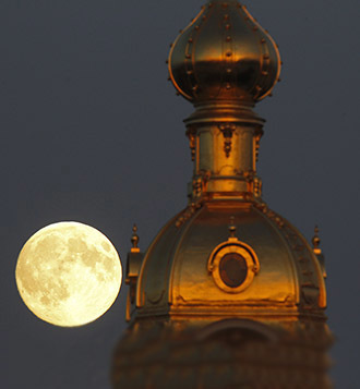 The moon rises behind the Peter and Pawel Fortress in St. Petersburg June 22, 2013. (Reuters / Alexander Demianchuk)