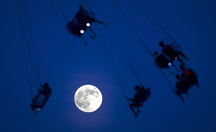 People ride the Luna Park Swing Ride as the Super Moon rises on Coney Island, June 22, 2013. (Reuters / Carlo Allegri)
