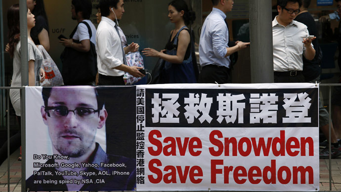 People carrying mobile phones walk past a banner supporting Edward Snowden, a former contractor at the National Security Agency (NSA), at Hong Kong's financial Central district June 18, 2013. (Reuters)