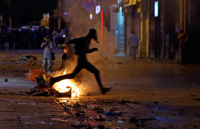 A protester jumps over a fire as he runs from riot police on a street near Taksim Square in Istanbul June 22, 2013 (Reuters / Marko Djurica)