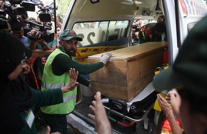 Pakistani rescuers shift a coffin of a foreign tourist from an ambulance to a hospital in Islamabad on June 23, 2013. (AFP Photo / Farooq Naeem)