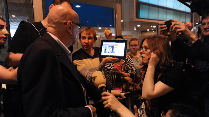 A journalist shows to a passenger a picture of former US spy Edward Snowden on a tablet, at the arrival gate of the Moscow Sheremetevo airport on June 23, 2013. Snowden arrived on June 23, 2013.(AFP Photo / Vasily Maximov)