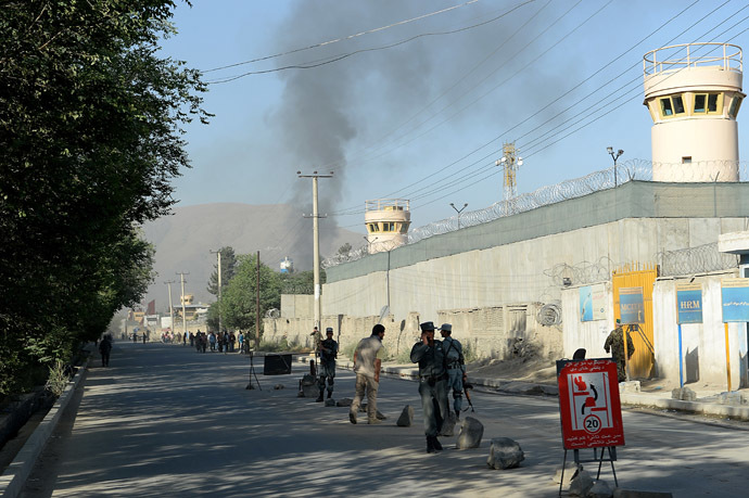 Afghan security forces stand guard as smoke rises from the entrance gate of the Presidential palace in Kabul on June 25, 2013. (AFP Photo)