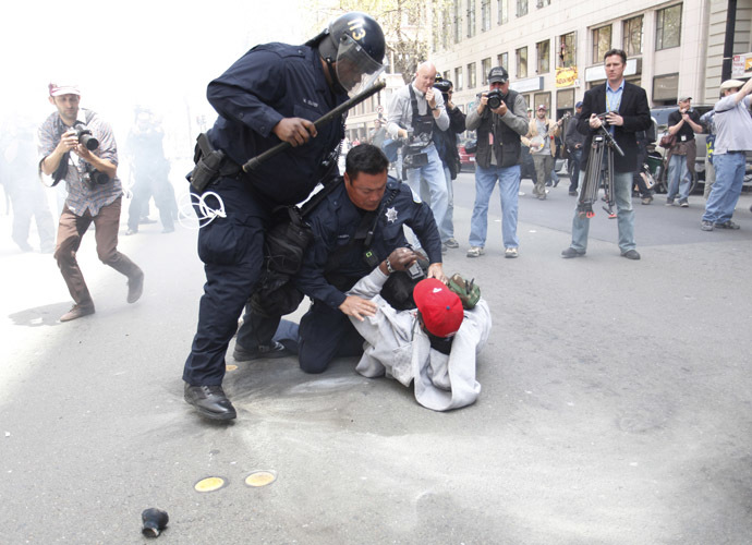 Oakland police officers try to detain an Occupy Oakland protester near City Hall in downtown Oakland, California, during the May Day protest on May 1, 2012. (AFP Photo/Kimihiro Hoshino)