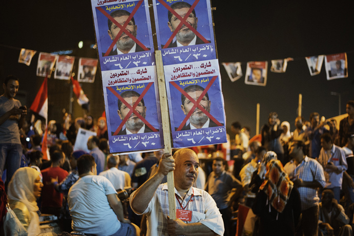 An Egyptian man holds a placard as hundreds of Egyptian anti-government protesters shout political slogans against Egyptian President Mohammed Morsi in Egypt's landmark Tahrir square as they watch Morsi's speech protesting against government and the Muslim Brotherhood on June 26, 2013 in Cairo, Egypt (AFP Photo / Gianluigi Guercia)