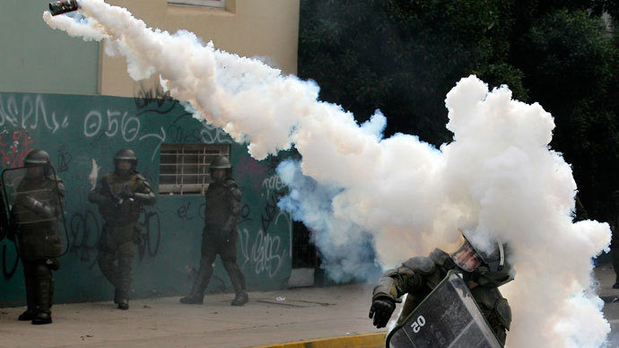 A riot police officer throws a tear gas canister at students during a demonstration against the government to demand changes in the public state education system in Valparaiso city, about 121 km (75 miles) northwest of Santiago, June 26, 2013.(Reuters / Eliseo Fernandez)
