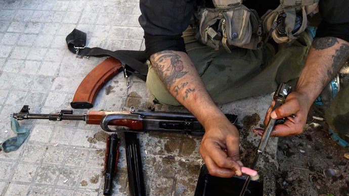 A Free Syrian Army fighter cleans his weapons.(Reuters / Muzaffar Salman)