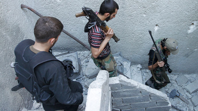 Members of the Free Syrian Army walk down the stairs holding their weapons in Aleppo's Salaheddine district.(Reuters / Hamid Khatib)