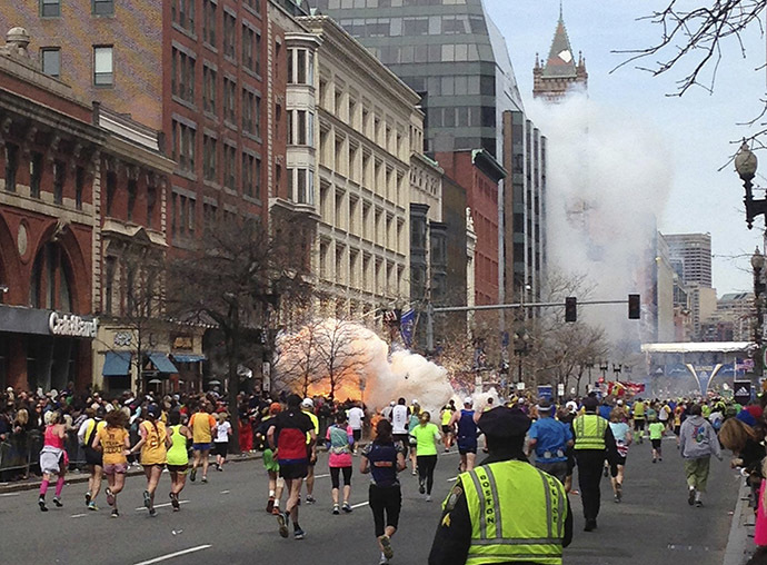 Runners continue to run towards the finish line of the Boston Marathon as an explosion erupts near the finish line of the race in Boston, Massachusetts, April 15, 2013. (Reuters / Dan Lampariello)