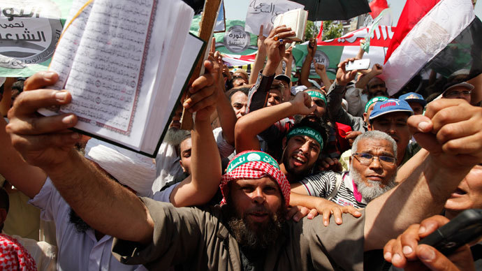 Islamists, members of the brotherhood, and supporters of Egyptian President Mohamed Morsi shout slogans holding the Holy Quran during a protest around the Raba El-Adwyia mosque square in the suburb of Nasr City, Cairo, June 28, 2013.(Reuters / Mohamed Abd El Ghany)