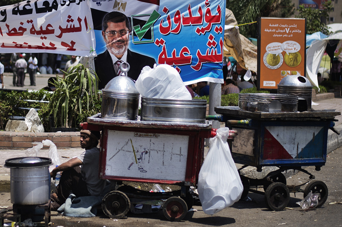 A street vendor sits by his cart as supporters of Egyptian President Mohamed Morsi and the Muslim Brotherhood camp outside the Rabaa al-Adawiya mosque in Cairo during a sit-in to show their support to Morsi on June 29, 2013 (AFP Photo / Gianluigi Guercia)