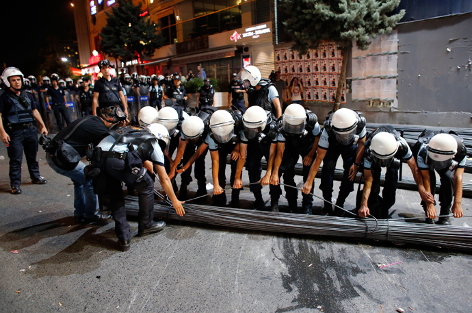 Riot police remove iron bars from a barricade to open the road to the traffic during an anti-government protest at Taksim Square in Istanbul June 29, 2013 (Reuters / Umit Bektas)