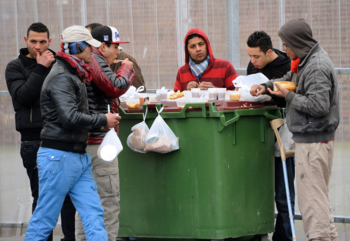 "Illegal immigrants eat on February 28, 2013 meals distributed by the ""La Belle Etoile"" (Pretty Star) association in the port of the northwestern French city of Calais. (AFP Photo / Philippe Huguen)"