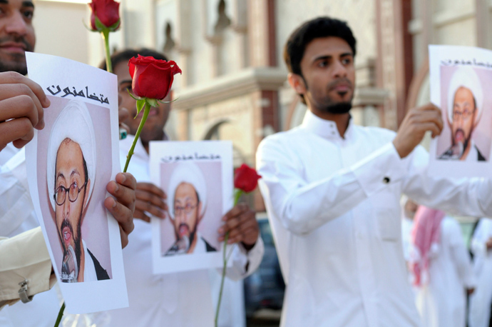 Supporters of Saudi Shi'ite cleric Tawfiq al-Amer hold his pictures during a demonstration following his release in Al-Ahs (Reuters / Stringer)