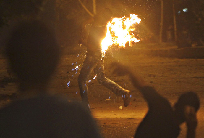 A protester who opposes Egyptian President Mohamed Morsi runs after a Molotov cocktail burns him during the attack of national headquarters of the Muslim Brotherhood in Cairo's Moqattam district June 30, 2013. (Reuters)