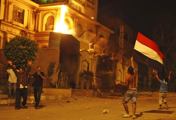 Protesters opposing Egyptian President Mohamed Morsi wave an Egyptian flag and shout slogans against him and members of the Muslim Brotherhood after attacking its national headquarters Molotov cocktails in Cairo's Moqattam district June 30, 2013. (Reuters)