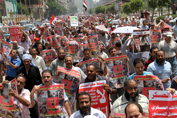 "Thousands of supporters of ousted Egyptian president Mohamed Morsi march towards Cairo University during a protest in his support on July 12, 2013 as they hold posters reading ""Down with the military rule"" and ""No to treason, no to military coup"" along with pictures of fellow Muslim Brotherhood supporters who were killed in clashes with security forces earlier this week (AFP Photo)"
