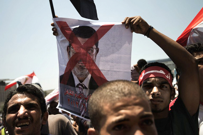 An Egyptian opposition supporter holds a crossed-out picture of President Mohammed Morsi (AFP Photo / Gianluigi Guercia)