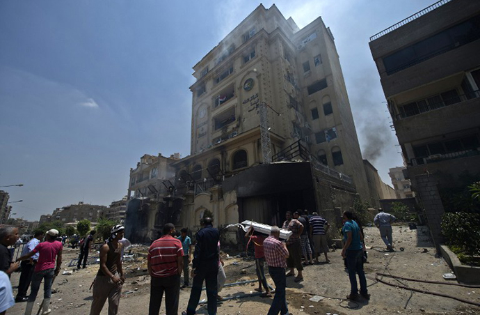 Egyptians gather outside the burnt headquarters of the Muslim Brotherhood in the Moqattam district of Cairo on July 1, 2013 after it was set ablaze by opposition demonstrators overnight. (AFP Photo / Khaled Desouki)