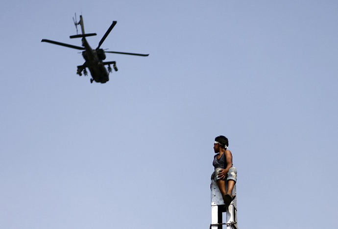 A military helicopter fly by, as protesters (unseen) call for the ouster of President Mohamed Morsi outside the presidential palace in Cairo, on July 2, 2013. (AFP Photo / Mahmud Khaled)