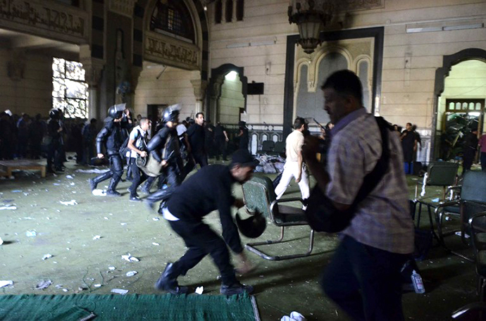 Egyptian riot policemen get in the community services hall of Cairo's Al-Fath mosque where Islamist supporters of ousted president Mohamed Morsi held up (AFP Photo / Mohamed El-Shahed)