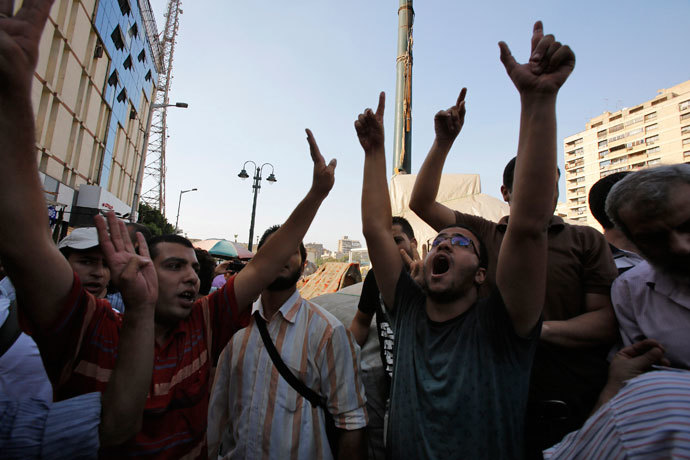 Supporters of the Muslim Brotherhood and ousted Egyptian President Mohamed Mursi shout slogans against the military and interior ministry as one gestures a 'four' during a protest in front of Al Istkama mosque at Giza Square, south of Cairo, August 19, 2013.(Reuters / Youssef Boudlal)
