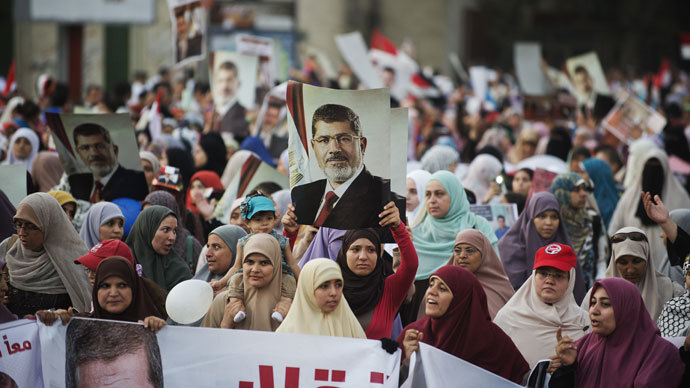 Egyptian women from the Muslim Brotherhood hold portraits of ousted President Mohammed Morsi as they march in his support on August 11, 2013 in Cairo.(AFP Photo / Gianluigi Guercia)