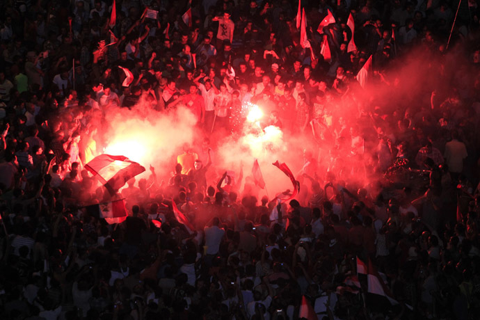 Protesters opposing Egyptian President Mohamed Morsi gather near a lit a flare during a protest at Tahrir Square in Cairo June 30, 2013. (Reuters)