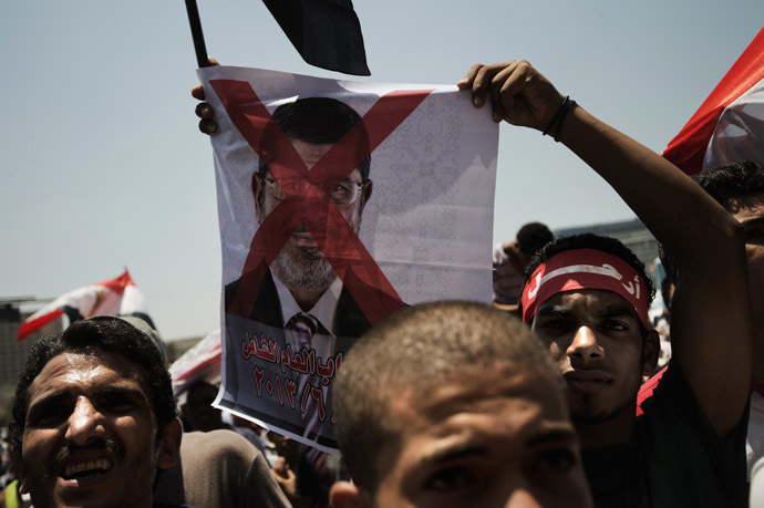 An Egyptian opposition supporter holds a crossed-out picture of President Mohammed Morsi as hundreds gather for a demonstration against Morsi and the Muslim Brotherhood in Cairo's landmark Tahrir Square on June 29, 2013. (AFP Photo)