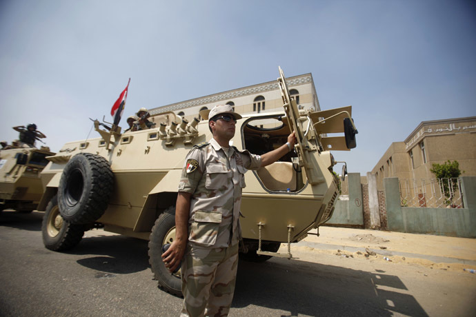 An army officer stands by an armoured personnel carrier deployed on a road leading to the Raba El-Adwyia mosque square where supporters of Egypt's deposed President Mohamed Morsi are camping, in Cairo July 4, 2013. (Reuters/Khaled Abdullah)