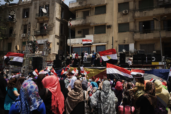 Egyptians cheer and wave their national flag as they gather in Cairo's landmark Tahrir square after a night of celebrations following the toppling of ousted Egyptian president Mohammed Morsi on July 4, 2013. (AFP Photo/Gianluigi Guercia)