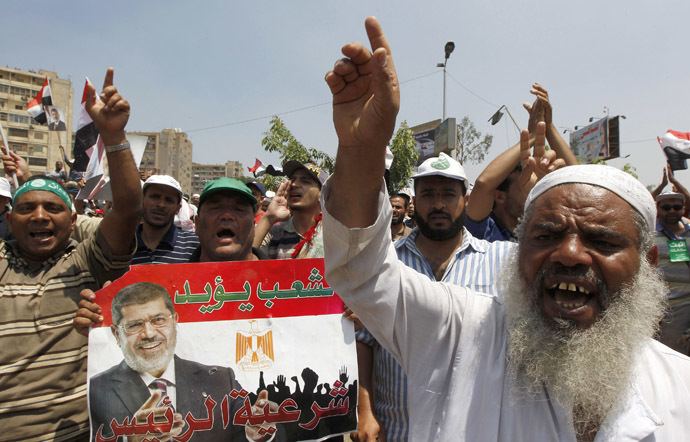 Members of the Muslim Brotherhood and supporters of ousted Egyptian President Mohamed Morsi hold a poster of him as they shout slogans at the Raba El-Adwyia mosque square in Cairo July 4, 2013. (Reuters/Louafi Larbi)