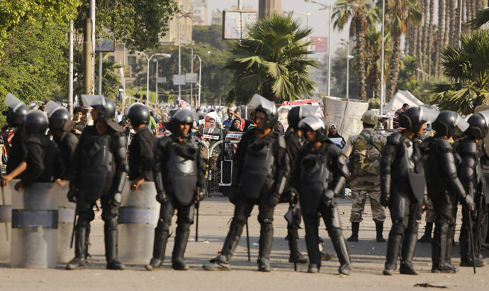 Protesters supporting former Egyptian President Mohamed Morsi demonstrate behind riot policemen near Cairo University in Cairo July 4, 2013. (Reuters/Suhaib Salem)