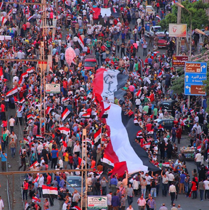 A group marches around the presidential palace protest carrying a huge Egyptian flag. (Photo from Instagram/@RT)