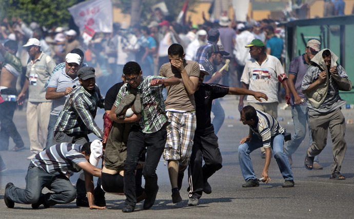 Supporters of ousted Egyptian president Mohamed Morsi evacuate a man who was shot during a gun battle outside the Cairo headquarters of the Republican Guard on July 5, 2013. (AFP Photo/Mahmud Hams)