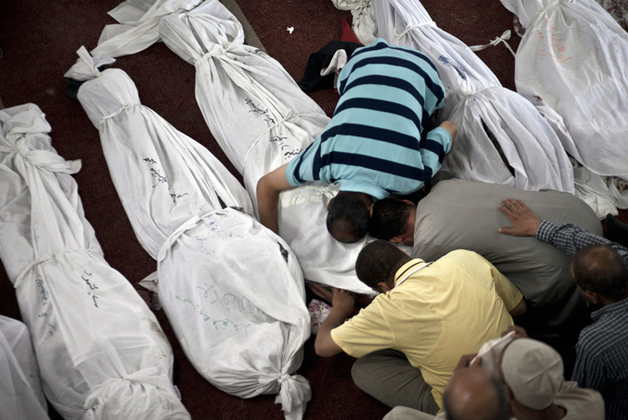 Egyptians mourn over a body wrapped in shrouds at a mosque in Cairo on August 15, 2013, following a crackdown on the protest camps of supporters of ousted Islamist president Mohamed Morsi the previous day (AFP Photo / Mahmoud Khaled)
