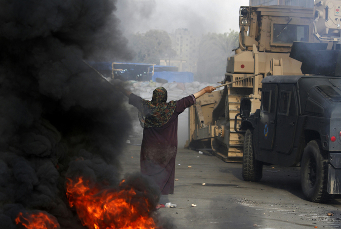 An Egyptian woman tries to stop a military bulldozer from going forward during clashes that broke out as Egyptian security forces moved in to disperse supporters of Egypt's deposed president Mohamed Morsi in a huge protest camp near Rabaa al-Adawiya mosque in eastern Cairo on August 14, 2013 (AFP Photo / Mohammed Abdel Moneim)