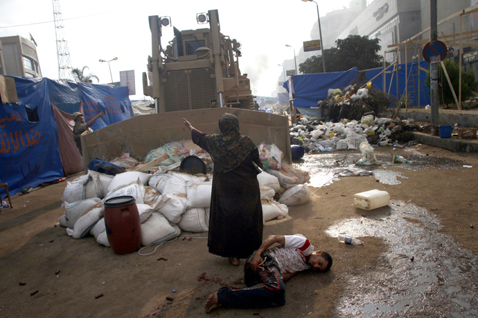 An Egyptian woman tries to stop a military bulldozer from hurting a wounded youth during clashes that broke out as Egyptian security forces moved in to disperse supporters of Egypt's deposed president Mohamed Morsi in eastern Cairo on August 14, 2013 (AFP Photo / Mohammed Abdel Moneim)