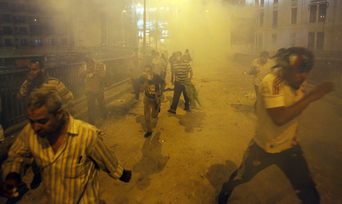 Supporters of deposed Egyptian President Mohamed Mursi run from tear gas fired by riot police during clashes at Ramses Square in Cairo, July 15, 2013 (Reuters / Amr Abdallah Dalsh)