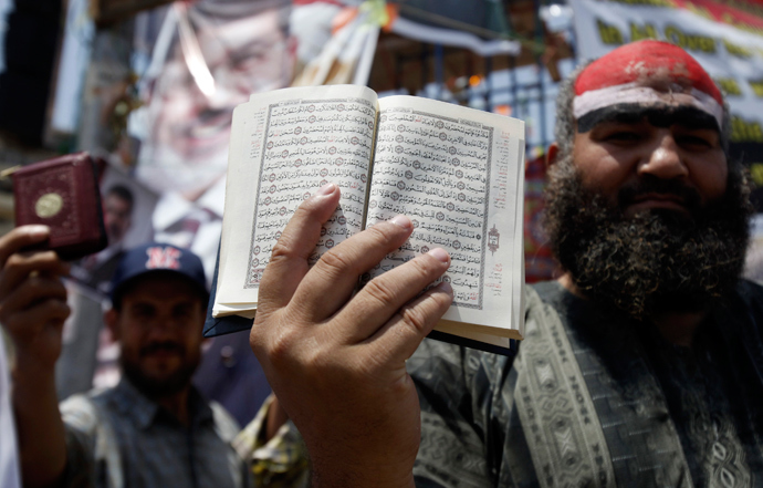 A supporter of deposed Egyptian President Mohamed Mursi holds a copy of the Koran during a protest at the Rabaa Adawiya square, where they are camping at, in Cairo July 11, 2013 (Reuters / Amr Abdallah Dalsh)