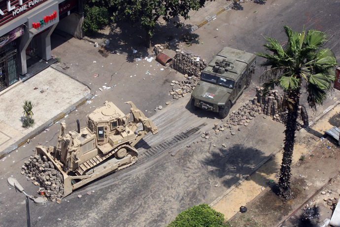 Army bulldozers remove a barricade errected by supporters of ousted president Mohamed Morsi during clashes with riot police at Cairo's Mustafa Mahmoud Square on August 14, 2013 (AFP Photo / Str)