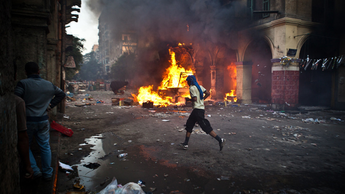A supporter of the Muslim Brotherhood and of ousted president Mohamed Morsi runs past a burning vehicle during clashes with security officers close to Cairo's Ramses Square, on August 16, 2013 (AFP Photo)