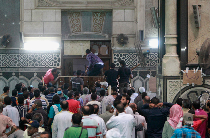 Demonstrators in support of ousted Egyptian President Mohamed Mursi wait by the barricaded door inside al-Fath mosque at Ramses Square in Cairo August 17, 2013 (Reuters / Mohamed Abd El Ghany)