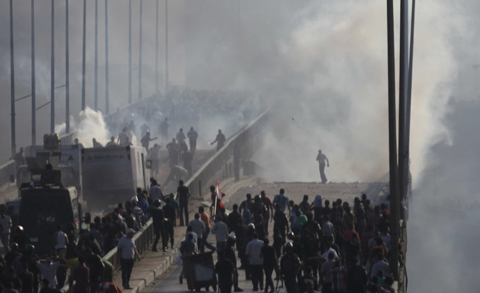 Members of the Muslim Brotherhood and supporters of ousted Egyptian President Mohamed Mursi flee from tear gas and rubber bullets fired by riot police during clashes, on a bridge leading to Rabba el Adwia Square where they are camping, in Cairo August 14, 2013. (Reuters/Amr Abdallah Dalsh)